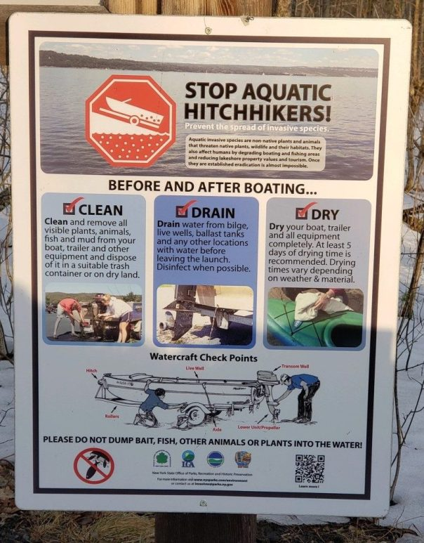 image showing a Stop Aquatic Hitchhikers sign at a boat cleaning station