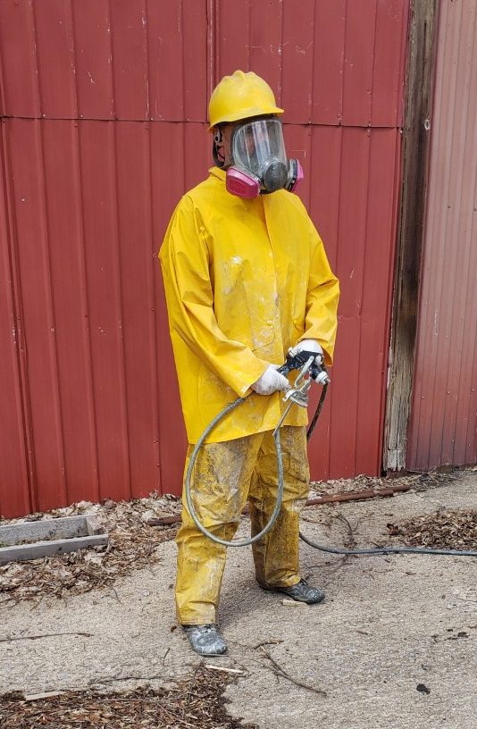 Man in yellow hazardous material suit with gas mask and spray gun